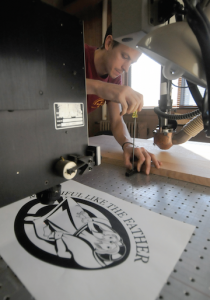 Benedictine Brother Lew Grobe sets up a test on the St. John's Abbey woodshop's laser engraver Nov.3 before the Year of Mercy logo is laser-cut onto a plaque that will identify the Holy Door at St. Mary's Cathedral in St. Cloud. Photo by Dianne Towalski / The Visitor