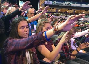 """Youth and chaperones from Becker/Big Lake, Minn. pray over featured speaker Chris Padgett during the Friday morning, Nov. 20 session at #ncyc2015 The morning focused on devotion to Mary and Padgett talked about Mary being the first to say """"Here I Am Lord,"""" the theme of this year's conference. Photo by Dianne Towalski / The Visitor"""